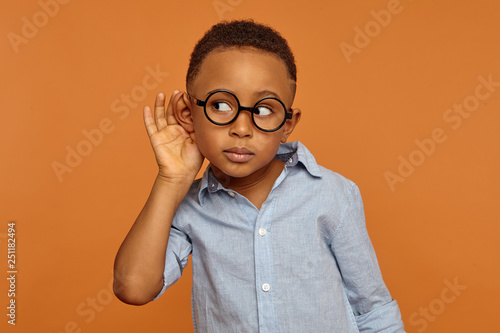 I want to hear everything. Handsome nosy African American little boy wearing round spectacles and neat shirt having curious facial expression while spying, overhearing, holding hand on his ear