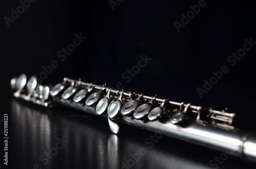 Leinwand Poster Glossy silver transverse flute on a black background