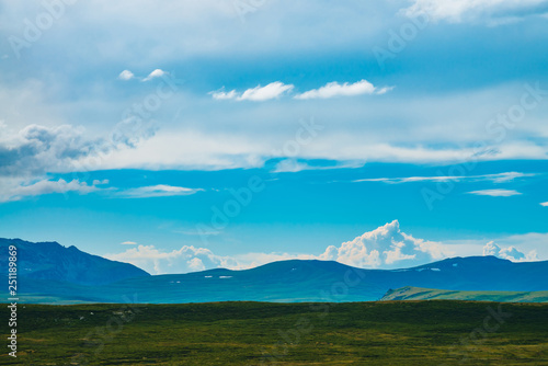 Fototapeta Spectacular view of giant mountains with snow. Huge cloud above mountain. Big rocky cliff above abyss. Wonderful wild scenery. Atmospheric highland landscape of majestic nature. Scenic mountainscape. obraz na płótnie