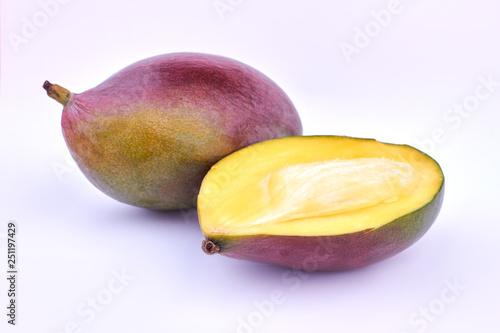Obraz Whole and half of ripe mango. Ripe mango fruit on light background. Juicy exotic fruit. - fototapety do salonu