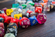 Various Plastic Polyhedral Game Dice Strewn About On A Wooden Table