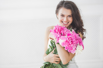 FototapetaClose up portrait of young beautiful woman with flowers indoors