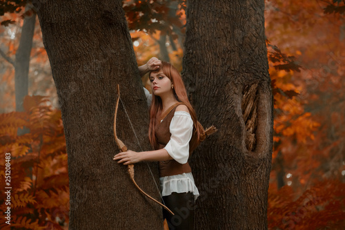 Photo mysterious girl with bright red hair between the trees in autumn woods, charming