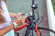 Girl Is Holding Smartphone, Searching Route Through Application In Internet Map. Against The Background Of Red Black Bicycle In Parking Lot. Online In Social Networks, Communication Correspondence.