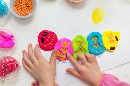 Obraz na plátně Little girl playing with plasticine