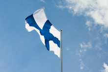National Flag Of Finland On Pole At Wind On Blue Sky And Clouds Background.