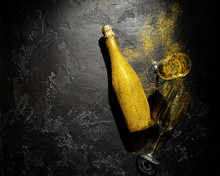 Romantic Image Of Golden Champagne Bottle, Two Wine Glasses On Black Background
