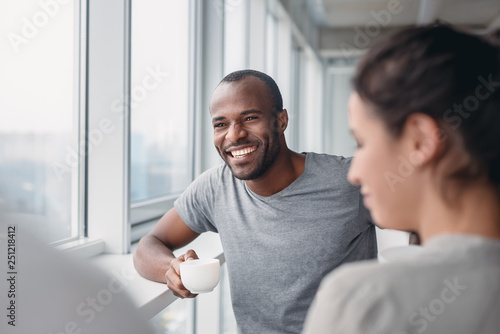 Foto  Multi-cultural colleagues are joking during coffee break at workplace