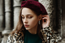Outdoor Close Up Fashion Portrait Of Young Beautiful Fashionable Lady Wearing Trendy Animal, Leopard Print Faux Fur Coat, Beret, Hoop Earrings, Posing In Street Of  European City