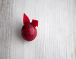 red egg with rabbit ears of felt on a wooden background