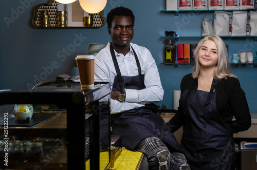 Foto  Two young multiracial baristas posing with a confident look in a coffee shop or
