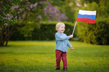 Cute Little Boy Holding Russian Flag During Walking In Summer Park