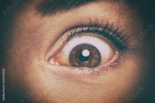 Eye peeking through peep hole watching something scary Canvas Print