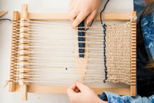 A Little Girl Learns Process To Weave Thick Threads. Hands Close Up.