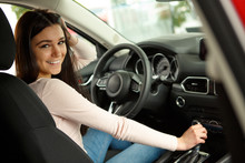 Side View Of Young Smiling Female Driver Sitting In Automobile Cabin On Comfortable Seats And Posing At Camera, Turning. Pretty Woman Holding Hand On Steering Wheel, Testing Auto.