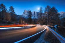 Blurred Car Headlights On Winding Road At Night In Autumn. Landscape With Asphalt Road, Light Trails, Mountains, Trees, And Blue Sky With Moon At Dusk. Roadway In Italy. View With Highway And Rocks