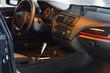 Dark luxury car Interior - steering wheel, shift lever and dashboard.