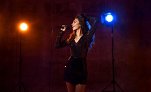 Beautiful Singing Girl Curly Afro Hair. Beauty Woman Singer Sing With Microphone Karaoke Song On Stage Smoke, Spotlights