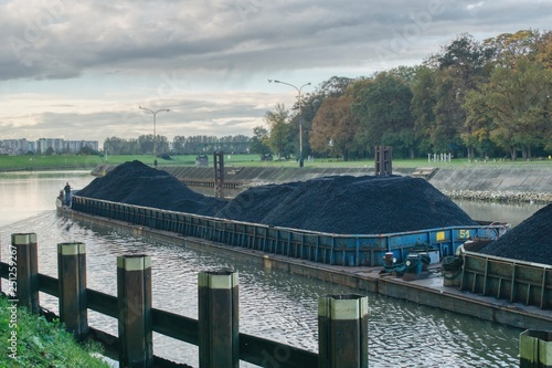 Fotografia  the barge flows along the river, transports coal to the power plant, repairing w