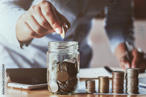 Fototapeta accountant saving money hand holding coins putting in jug glass. concept finance and accounting obraz