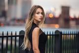 Fototapeta Nowy York - Beautiful woman with long blond hair walking in the city at evening time wearing elegant black dress