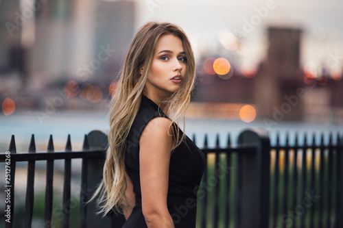 Slika na platnu Beautiful woman with long blond hair walking in the city at evening time wearing