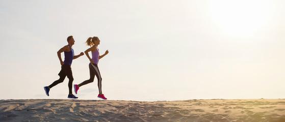 Siluete muškarca i žene koji trče u zalazak sunca