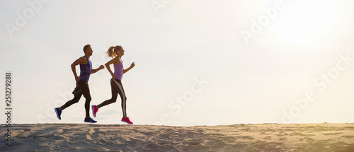 Foto  Silhouettes of man and woman running at sunset