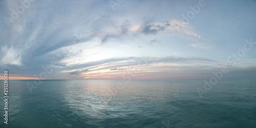 Fototapeta Colorful seascape. Twilight sunset over the sea with colorful clouds. Panorama of cloudy sky and aqua water obraz