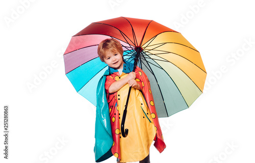 Fotografiet  Cheerful boy in raincoat with colorful umbrella