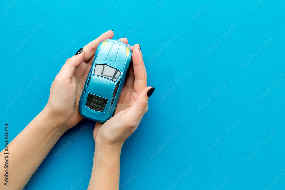 Fototapety, obrazy: Car insurance concept. Safety of auto. Car toy in female hands on blue background top view copy space