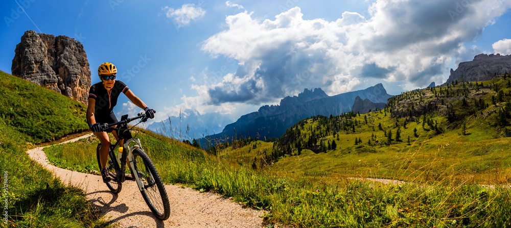 Fototapety, obrazy: Tourist cycling in Cortina d'Ampezzo, stunning Cinque Torri and Tofana in background. Man riding MTB enduro flow trail. South Tyrol province of Italy, Dolomites.