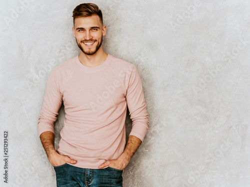 Fotografiet  Portrait of handsome smiling hipster lumbersexual businessman model wearing casual summer pink clothes