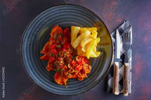 Foto  Portuguese  goulash with tomato and olives sauce and fried potato