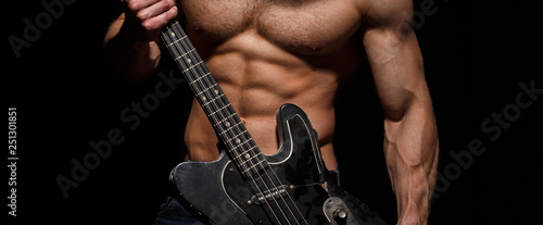 Torso man. Chest muscles, Six pack, ab, triceps. Electric guitar. Music festival. Instrument on stage and band. Strong, muscular, muscles man, bodybuilding. Music concept. Play the guitar. - 251301851