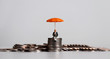 canvas print picture - Stack of coins and a miniature people with a orange umbrella.