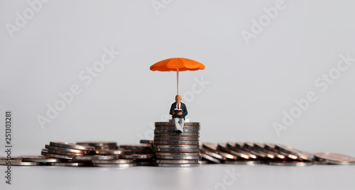 Fotomural  Stack of coins and a miniature people with a orange umbrella.