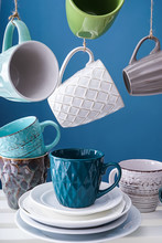 Shelf With Different Tea Cups And Saucers On Color Background