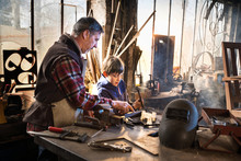 A Craftsman In His Workshop Teaches His Work To His Young Son