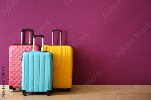 Fototapeta Packed suitcases near color wall obraz