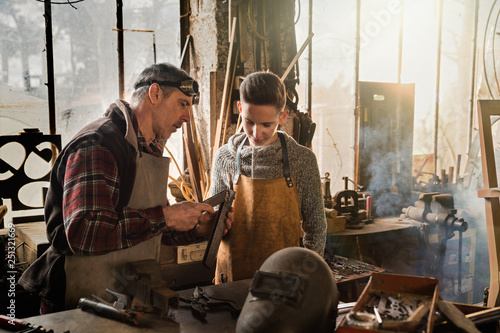 A craftsman in his workshop teaches his work to his apprentice Canvas Print