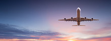 Commercial Airplane Jetliner Flying Above Dramatic Clouds In Beautiful Sunset Light. Travel Concept.