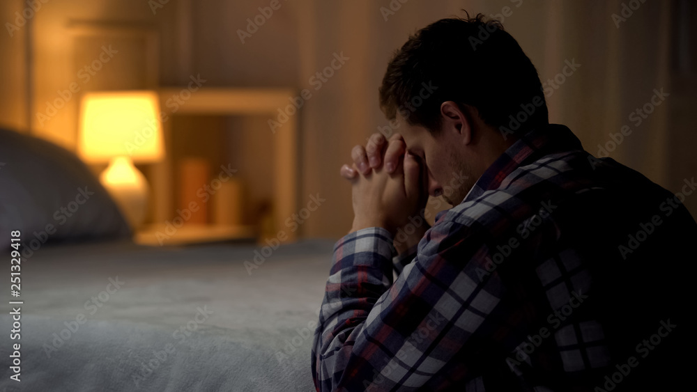 Fototapety, obrazy: Religious young man praying in evening near bed, belief in God, Christianity