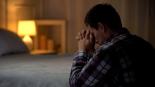 Religious Young Man Praying In Evening Near Bed, Belief In God, Christianity