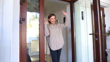 Mother Standing By Door And Waving Hand To Children Walking To School, Goodbye