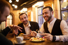 Group Of Cheerful Business People Enjoying Food And Conversation In Cafe, Copy Space