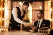 Portrait of handsome mature businessman reading menu in luxury restaurant talking to waiter, copy space