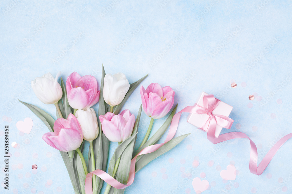 Fototapeta Women Day, Mother day background with gift box and beautiful spring tulip flowers on pastel blue table. Flat lay.