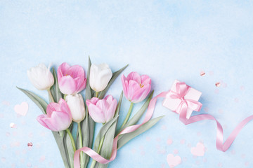 Women Day, Mother day background with gift box and beautiful spring tulip flowers on pastel blue table. Flat lay.