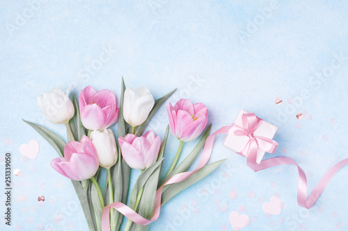 Obraz Women Day, Mother day background with gift box and beautiful spring tulip flowers on pastel blue table. Flat lay. - fototapety do salonu